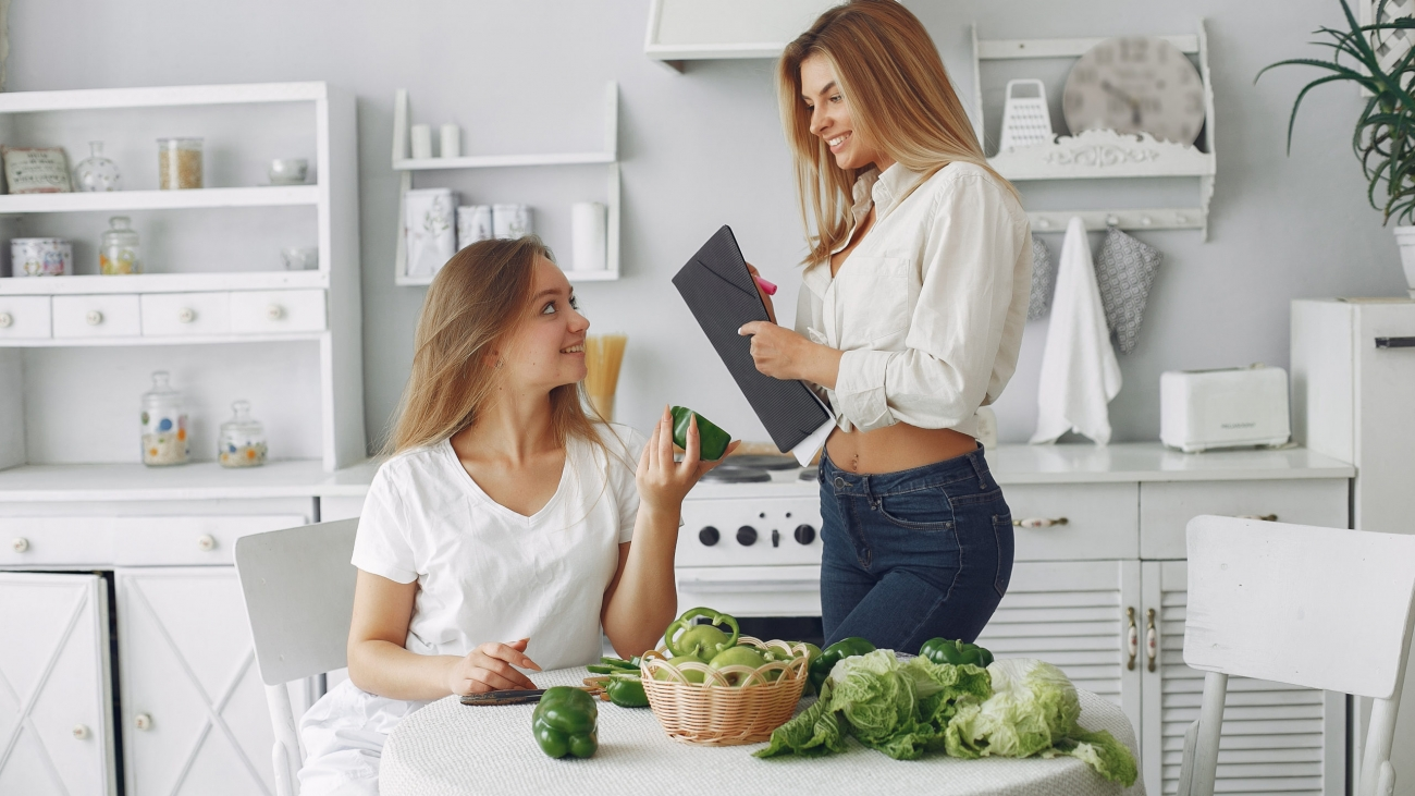 Beautiful and sporty girls in a kitchen with a vegetables